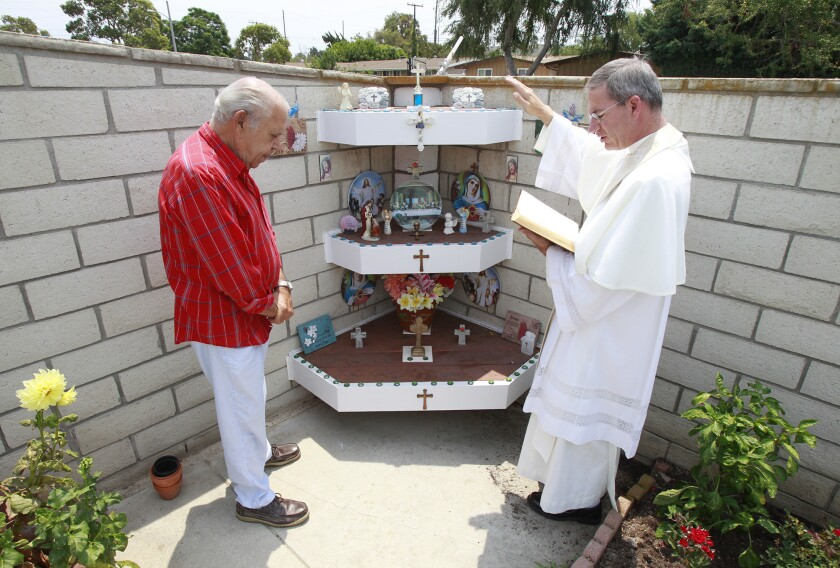Frank DeSimone, left, listens and prays as Father Augustine Puchner of St. John The Baptist Catholic Church blesses the altar at his home in Costa Mesa on Tuesday.