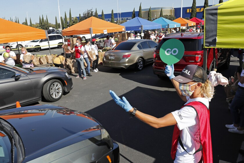 Volunteer Kelly Evans, right, directs traffic during a drive-through giveaway at IKEA in Costa Mesa, where 1,200 low-income families received emergency food boxes filled with essential staples such as rice, beans, pasta and fresh produce on Thursday.