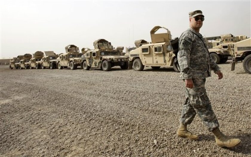 A U.S. army soldier walks past military Humvees which are ready to be shipped out of Iraq at a staging yard at Camp Sather, part of the sprawling U.S. military Victory Base Complex that is set to close in Baghdad, Iraq, Saturday, Oct. 15, 2011. The U.S. has promised to withdraw from Iraq by the end