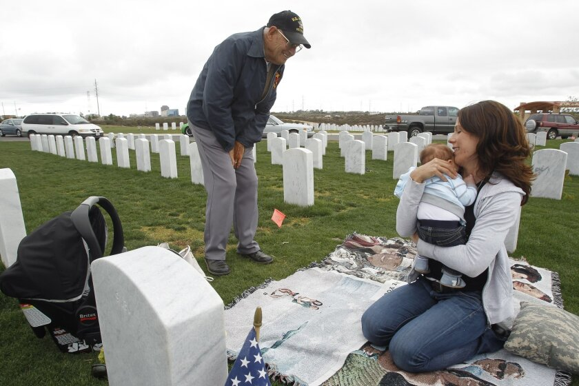 Navy veteran Raymond Moody, who came to visit his wife Barbara's grave, says hello to Jenn Budenz, holding her 2-month-old son AJ, as she visits the grave of her husband and father of her child Marine Major Andrew Budenz at the Miramar National Cemetery in San Diego on Thursday.