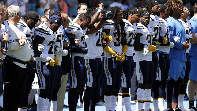 In a protest against President Trump's comments, the Chargers link arms during the national anthem before Sunday's game against the Kansas City Chiefs at StubHub Center.