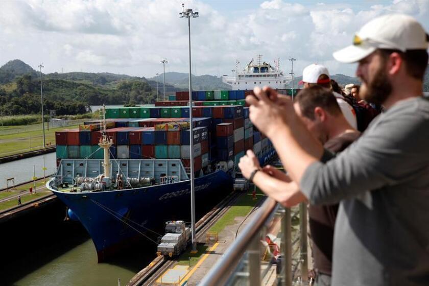 Turistas observan el tránsito de un buque portacontenedores de la naviera Cosco Shipping en las esclusas de Miraflores en el Canal de Panamá. EFE/Archivo