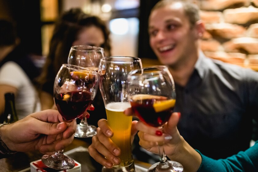 Group Of Friends Enjoying Evening Drinks In Bar. (iStock)