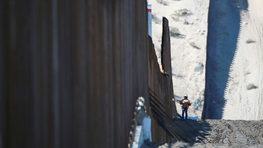 A worker is dwarfed by the border fence which is under construction Wednesday, Jan. 25, 2017, in Sunland Park, N.M. across from Anapra, in Ciudad Juarez, Mexico.