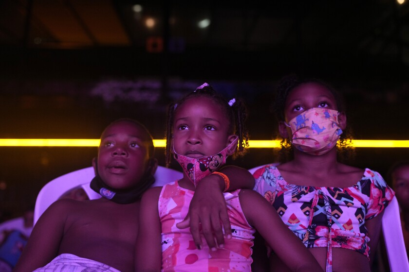 "Children watch a movie of the ""Cinema no Morro"" or Cinema on the hill project at a cultural center at the Vila Cruzeiro favela of Rio de Janeiro, Brazil, Monday, Sept. 13, 2021. The Cinema on the hill is a project provided by the Voz da Comunidade NGO, to screen movies for children from the favelas. (AP Photo/Silvia Izquierdo)"