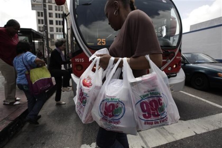 A woman carries her purchases in plastic bags in Los Angeles.