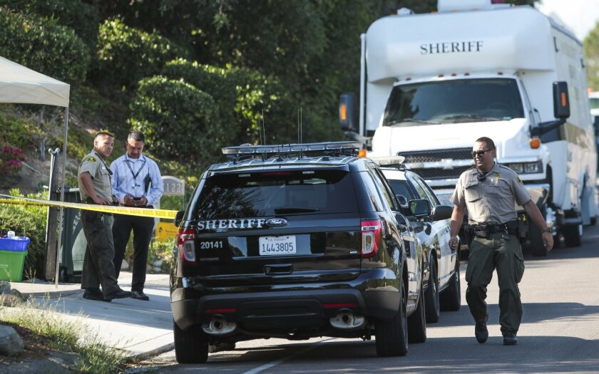 Sheriff's deputies in front of the home on Via de la Valle in Rancho Santa Fe where three people were found dead on Monday.
