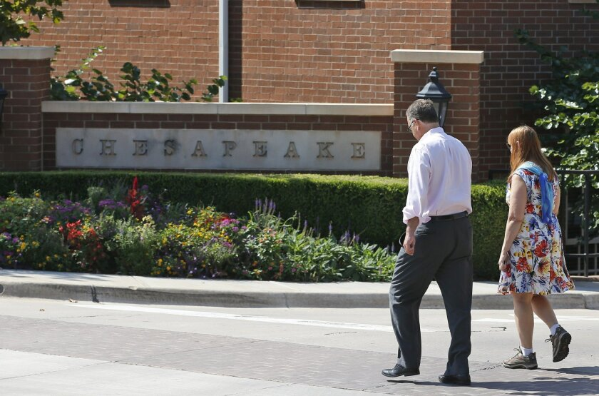 FILE - In this Tuesday, Sept. 29, 2015, file photo, two people walk past one of the entrances to the Chesapeake Energy Corporation campus in Oklahoma City. Chesapeake Energy sought to assure investors Monday, Feb. 8, 2016, that it is not planning to file for bankruptcy protection. The announcement