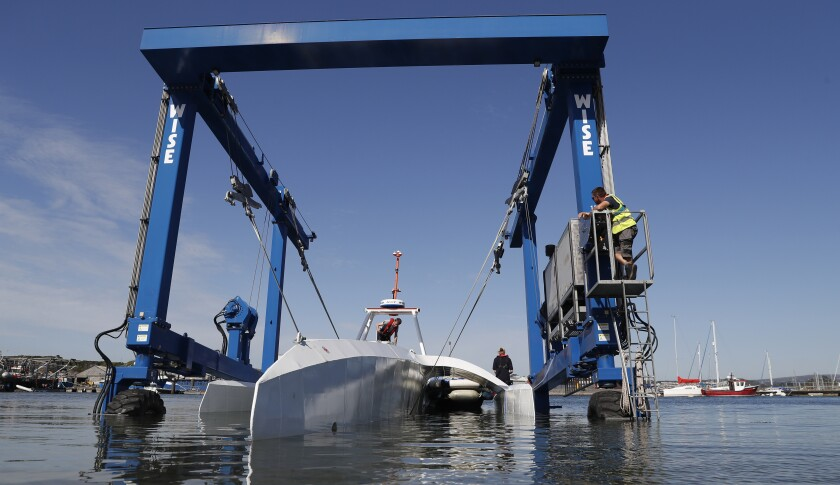 FILE - In this Monday, Sept. 14, 2020 file photo, technicians lower the Mayflower Autonomous Ship into the water at its launch site for it's first outing on water since being built in Turnchapel, Plymouth south west England. Four centuries and one year after the Mayflower departed from Plymouth, England on a historic sea journey to America, another trailblazing vessel with the same name has set off to retrace the voyage. It's being piloted by sophisticated artificial intelligence technology for a trans-Atlantic crossing that could take up to three weeks, in a project aimed at revolutionizing marine research. IBM, which built the ship with nonprofit marine research organization ProMare, confirmed the Mayflower Autonomous Ship began its trip early Tuesday June 15, 2021.(AP Photo/Alastair Grant, file)