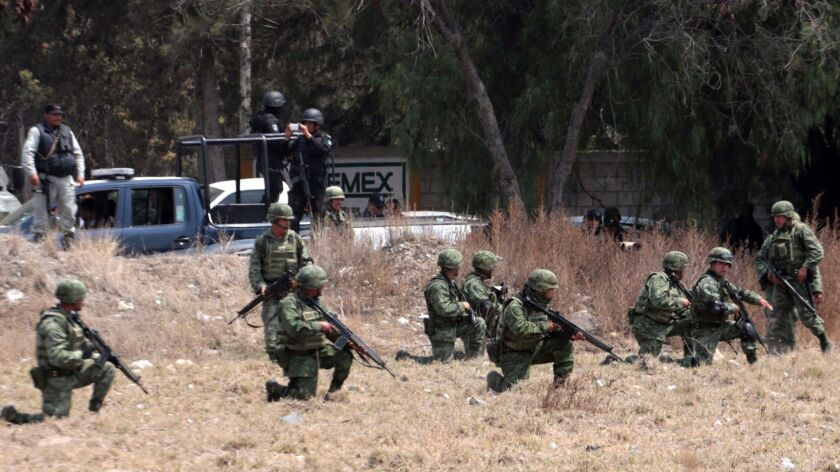 Soldiers take positions in front of villagers mounting roadblocks with burning tires to protest an army crackdown in Palmarito Tochapan, Mexico.
