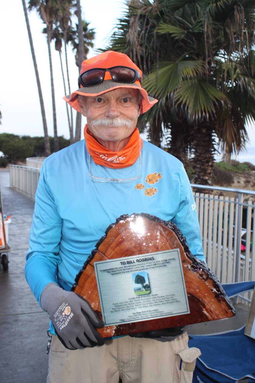 La Jolla resident Bill Robbins holds an award recognizing his community service around La Jolla Cove and Scripps Park.
