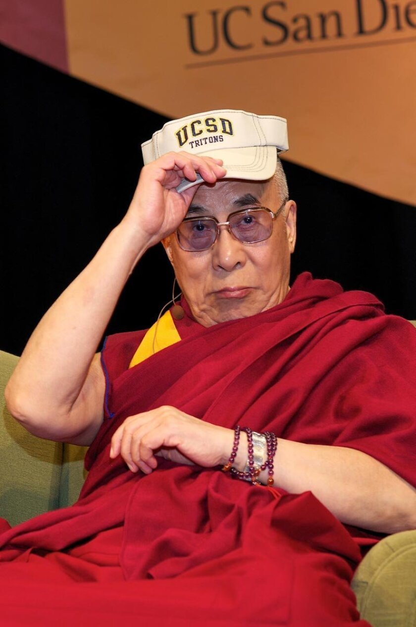 An affable Dalai Lama donned a UCSD Titans visor during a discussion on global climate change at UCSD. Photos by Carol Sonstein