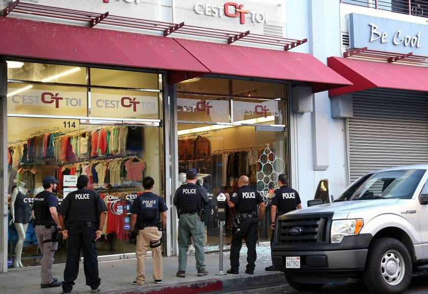 FILE - In this Wednesday, Sept. 10, 2014 file photo, law enforcement agents stand outside a clothing store after a raid in the Los Angeles Fashion District. Federal authorities on Thursday, Oct. 2, 2014, slapped new financial reporting rules on 2,000 businesses in the fashion district of Los Angeles in an effort to curtail suspected Mexican drug money laundering.(AP Photo/ Nick Ut, File)