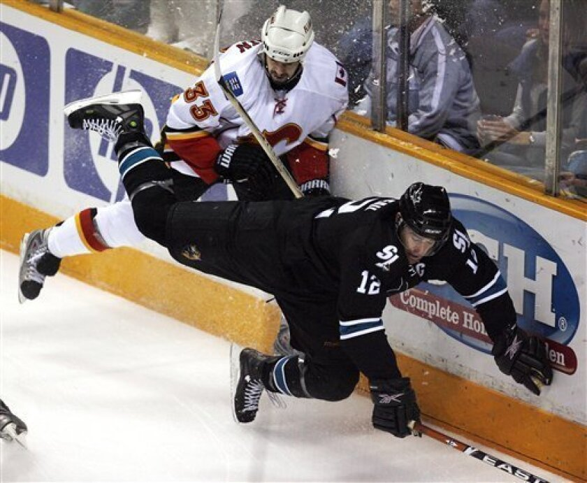 San Jose Sharks center Patrick Marleau, right, is checked into the boards by Calgary Flames defenseman Adrian Aucoin during the first period of an NHL hockey game in San Jose, Calif., Thursday, Jan. 15, 2009. (AP Photo/Tony Avelar)