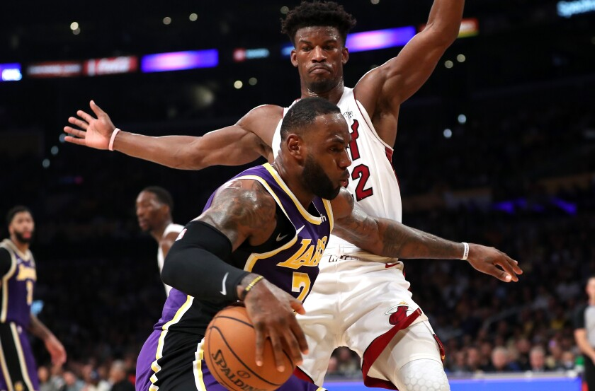 Lakers forward LeBron James tries to drive past Miami Heat forward Jimmy Butler