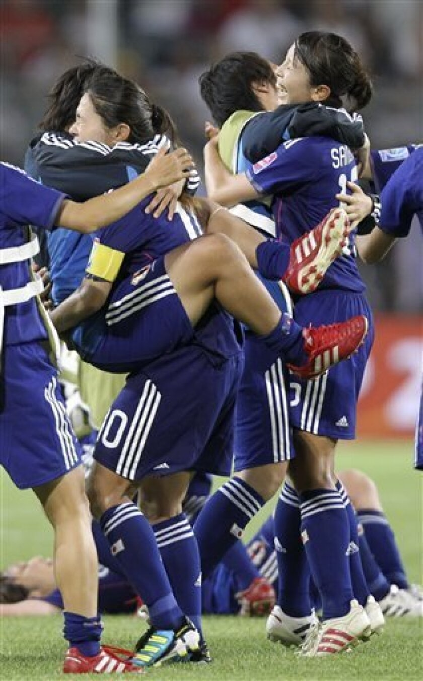 Japan's Homare Sawa, 2nd left, celebrates with players after Japan won 1-0 the quarterfinal match between Germany and Japan at the Women's Soccer World Cup in Wolfsburg, Germany, Saturday, July 9, 2011. (AP Photo/Michael Probst)