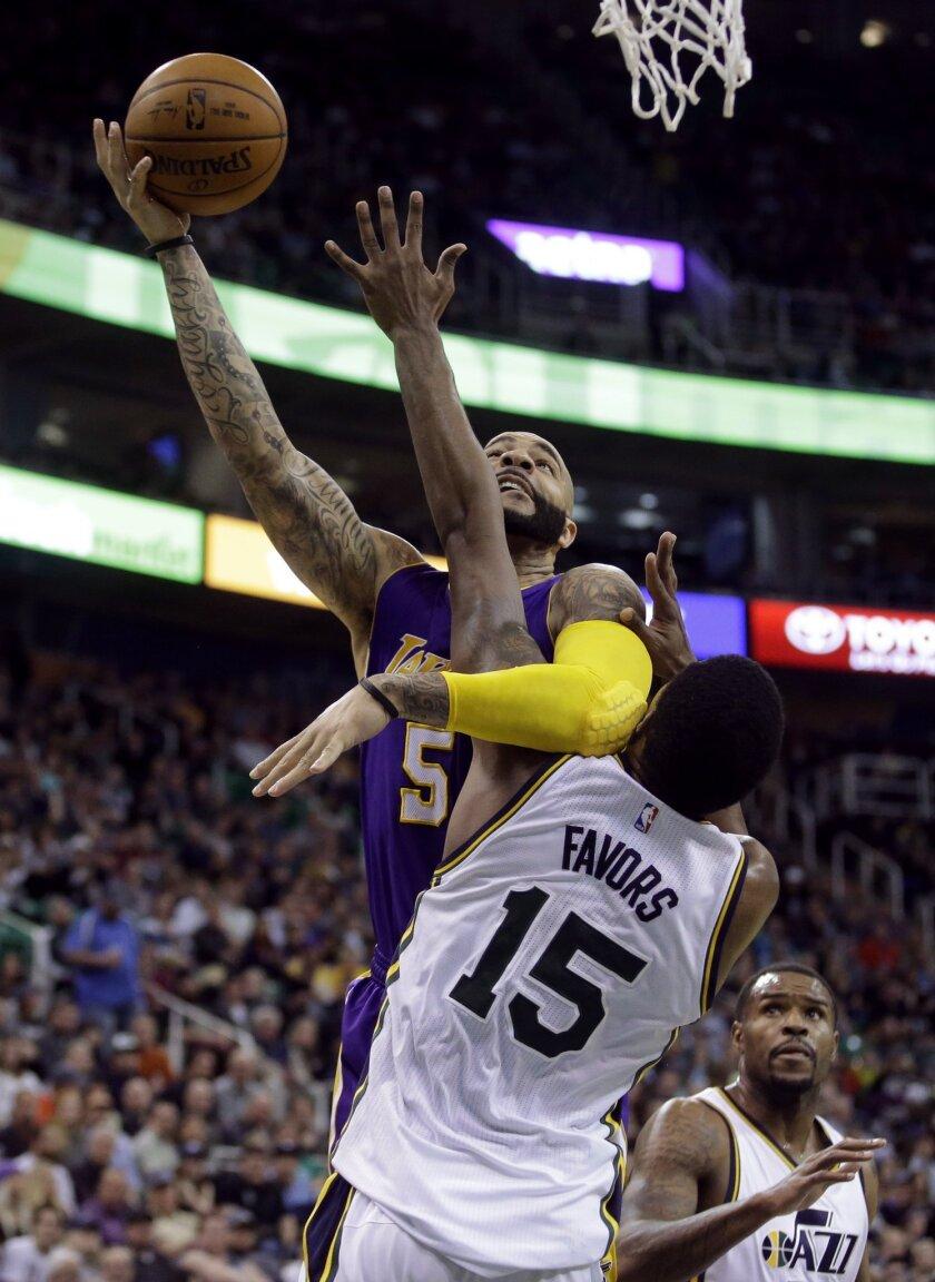 Utah Jazz forward Derrick Favors (15) defends against Los Angeles Lakers forward Carlos Boozer (5) in the second quarter of an NBA basketball game Wednesday, Feb. 25, 2015, in Salt Lake City. (AP Photo/Rick Bowmer)