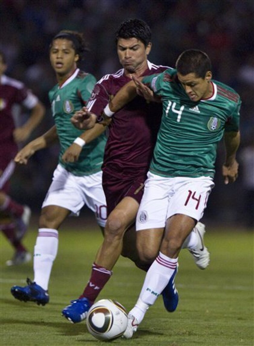 Mexico's Javier Hernandez, aka Chicharito, right, battles for the ball with Venezuela's Angel Chourio during a friendly soccer match at the Benito Juarez stadium in Ciudad Juarez, Mexico, Tuesday, Oct. 12, 2010. (AP Photo/Guillermo Arias)