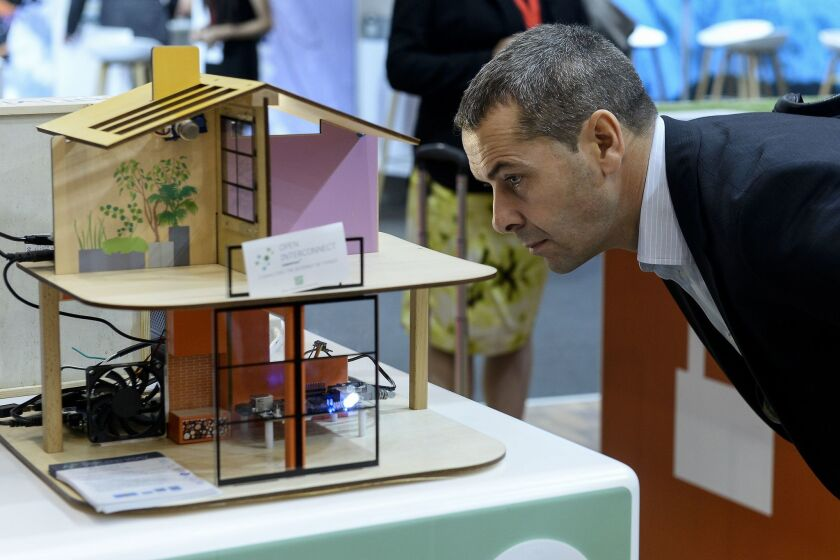 """A man views a model of a """"smart house"""" at the 2015 Internet of Things Solutions World Congress event in Barcelona on Sept. 16. The three-day conference featured key companies and institutions working in the rapidly growing field of Internet-connected devices."""