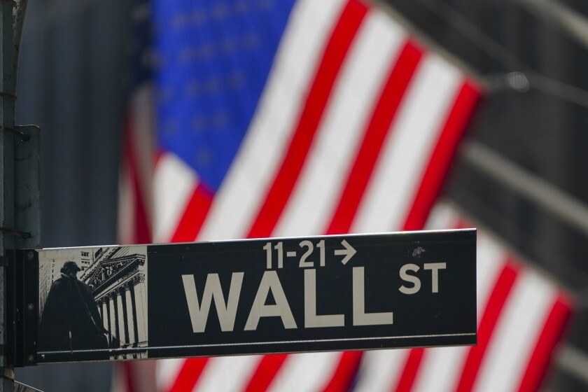 FILE - In this Wednesday, Oct. 14, 2020 file photo, the American Flag hangs outside the New York Stock Exchange in New York. Stocks are opening higher on Wall Street, putting the market on track to end a choppy week of trading slightly higher. If the gains hold, the S&P 500 would mark its third straight weekly gain. In the first few minutes of trading Friday, Oct. 16 the benchmark index was up 0.4%. (AP Photo/Frank Franklin II)