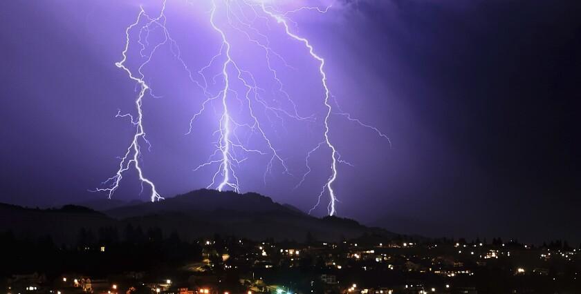 A lightning strike turns the night sky many shades of purple