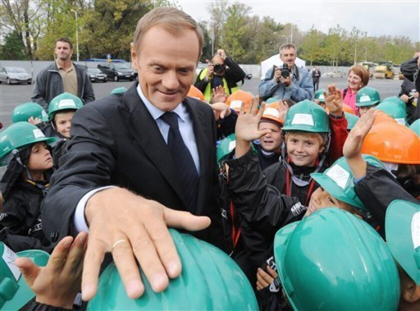 Polish Prime Minister Donald Tusk pats on the head a young soccer player during a meeting with children at the National Stadium construction site, in Warsaw, Poland, Friday, Oct. 7, 2011. Tusk's centrist ruling party was campaigning hard to maintain its lead before weekend elections in Poland, fending off challenges from a new socially liberal party and a traditional rival that has accused it of responsibility for a plane crash that killed a generation of top politicians. (AP Photo/Alik Keplicz)