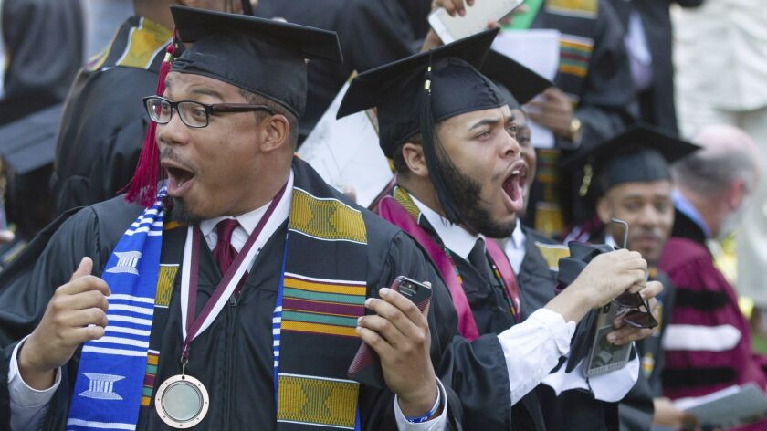 Graduates react after hearing billionaire technology investor and philanthropist Robert F. Smith say
