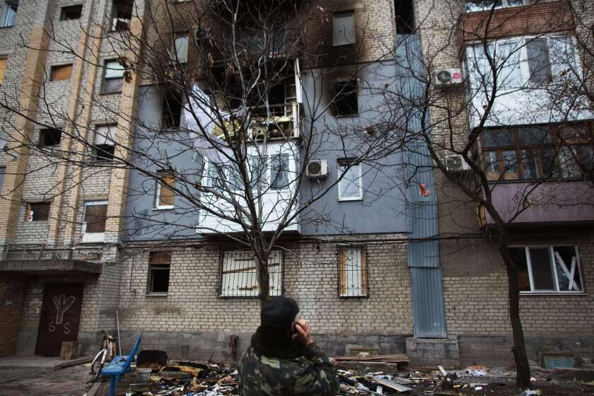 A man looks at an apartment block damaged by shelling in the eastern Ukrainian city of Donetsk on Monday. The continued fighting in Ukraine has strained Russia's relationships with European nations.