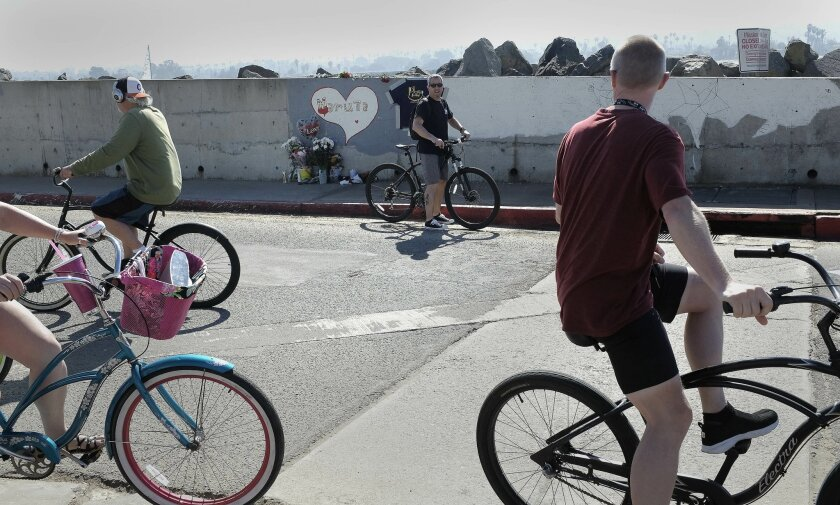 Bicyclists pass by a memorial wall for Maruta Gardner, killed in an accident Friday while she was removing graffitti from a wall at the south end of Mission Blvd. in Mission Beach.
