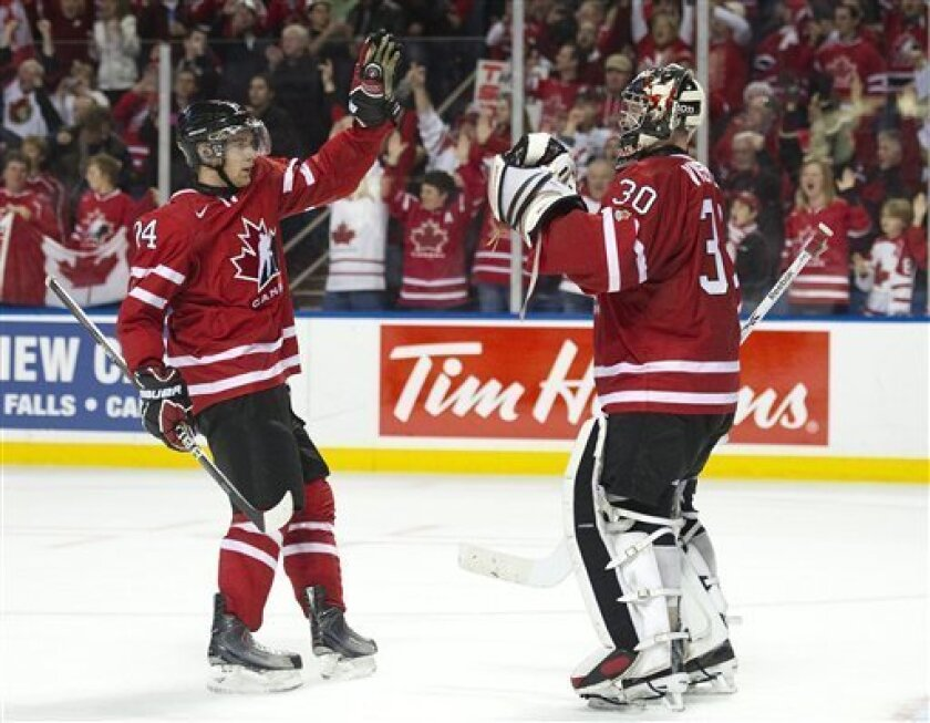 Canada's Calvin de Haan, left, celebrates with goalie Mark Visentin, right, after Canada defeated the United States 4-1 in a World Junior Hockey Championship game in Buffalo, N.Y., on Monday, Jan. 3, 2011. (AP Photo/The Canadian Press, Frank Gunn)