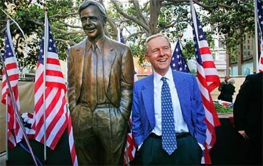 Pete Wilson stands by his bronze statue in downtown San Diego.