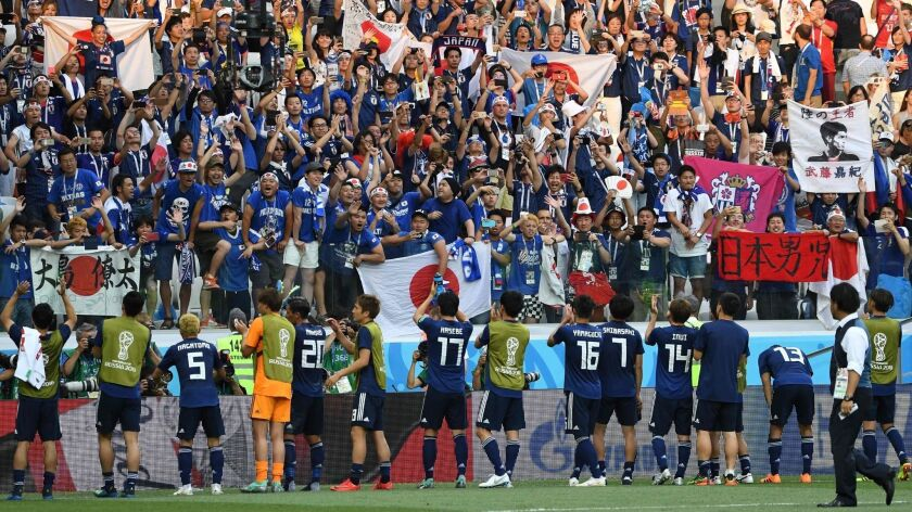"""Japan's players """"celebrate"""" a 1-0 loss against Poland, which was still enough to secure qualification for the second round of the World Cup."""
