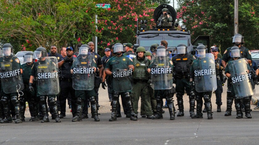 Sheriff's deputies watch protesters gathering against another group of protesters Sunday in Baton Rouge, La.