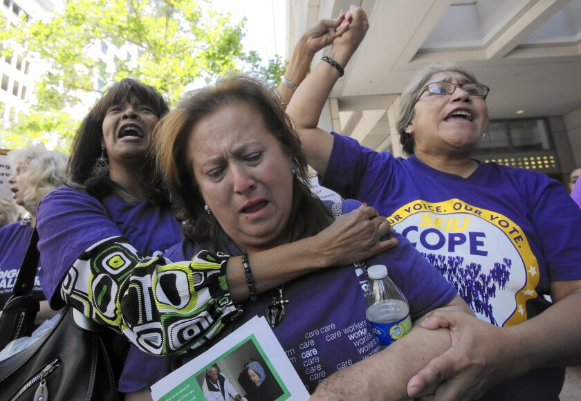 Home-care workers Juanita Williams, Zoila Ramirez and Bethzalie Saldana take part in a protest rally in downtown Los Angeles in 2014. The workers and their unions have fought for the right to be paid overtime.