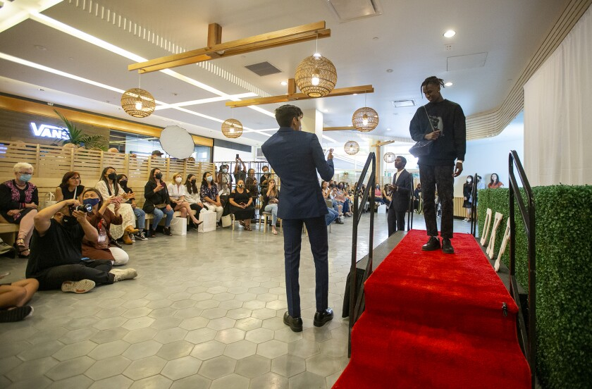 """Wesley Kuria models a bag designed by Team Greenprint at a """"Young people in fashion"""" fundraiser for a fashion show at South Coast Plaza."""