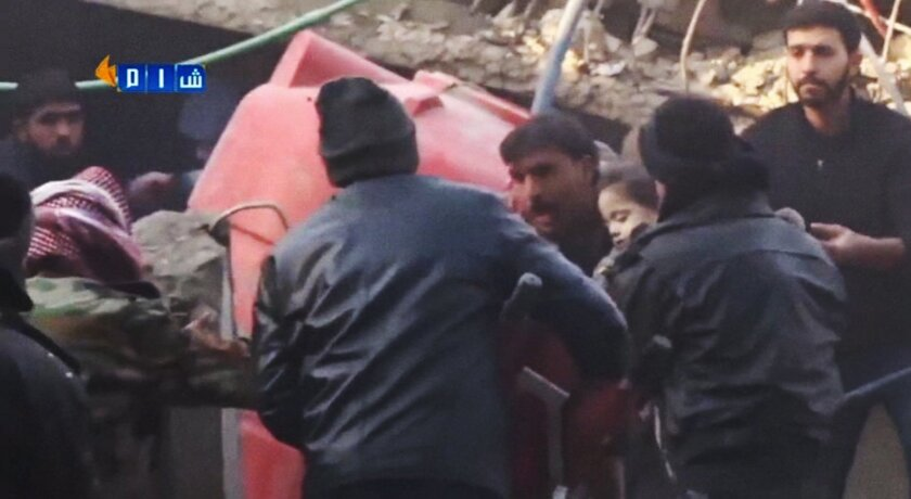 In this image made from Tuesday, Jan. 7, 2014, amateur video released by Ugarit News, which has been authenticated based on its contents and other AP reporting, people carry a girl out of rubble in Douma, Syria. In the town close to the Syrian capital of Damascus, several people were killed and wounded after a government airstrike targeted a house on Tuesday, reported the Observatory and another activist group, the Local Coordination Committees. (AP Photo/Ugarit News via AP Video)