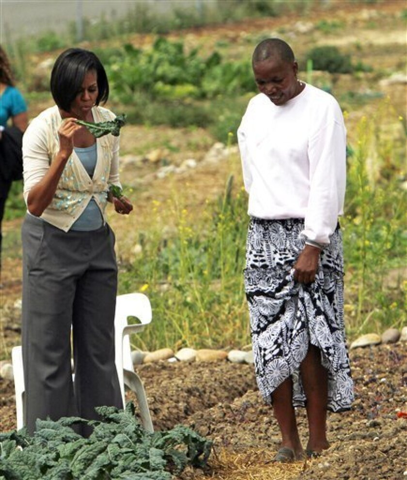 First Lady Michelle Obama, left, holds vegetables grown by Zimbabwe immigrant TsiTsi Mutseta at the New Roots Community Farm Thursday April 15, 2010 in San Diego. (AP Photo/Lenny Ignelzi)