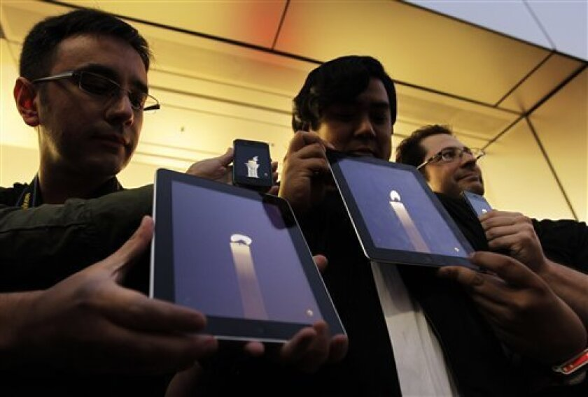 Apple computer fans hold their iPhones and iPads displaying candle graphics during a candle light vigil to pay tribute to Steve Jobs, the Apple founder and former CEO, at an Apple Store in the Ginza shopping district in Tokyo Thursday, Oct. 6, 2011. Apple announced Jobs' death without giving a specific cause. He died on Wednesday at the age of 56. (AP Photo/Hiro Komae)