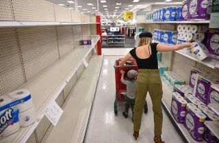 A shopper picks up a roll of toilet paper at a store in Burbank, California, November 19, 2020. - Paper towels and other cleaning supplies are flying off retail shelves amidst a new wave of panic buying as the country faces the most recent recent surge in coronavirus infections. (Photo by Robyn Beck / AFP) (Photo by ROBYN BECK/AFP via Getty Images)