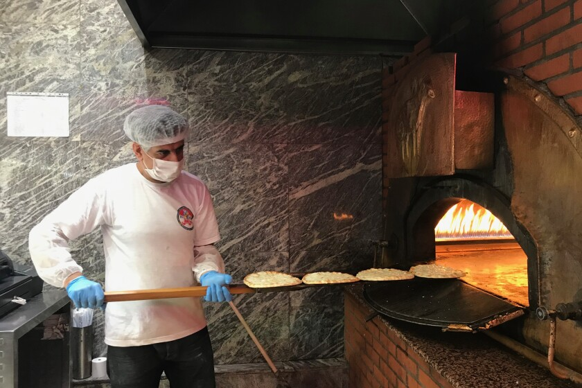 Kamal, one of Barbar's employees, tends to the fire-brick oven while making Manousheh, a Lebanese flatbread pizza