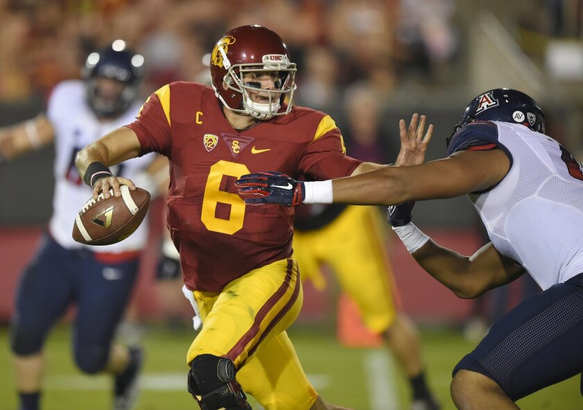 Southern California quarterback Cody Kessler, left, tries to hold off Arizona defensive lineman Reggie Gilbert during the first half of an NCAA college football game, Saturday, Nov. 7, 2015, in Los Angeles. (AP Photo/Mark J. Terrill)