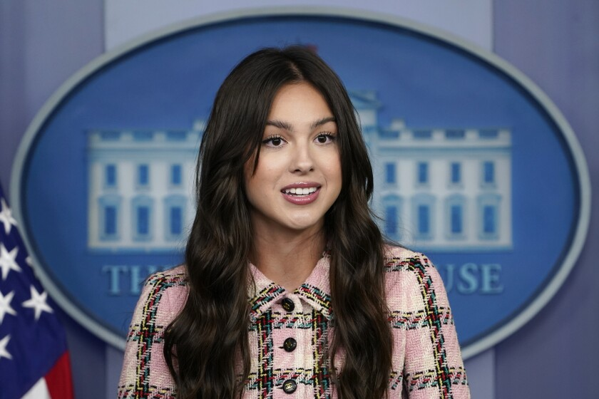 A young woman with long, brown hair speaks in front of the White House seal