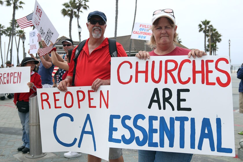 Wally Thomas of Lake Forest and Denean MacAndrew of Mission Viejo take part in a protest in Huntington Beach. More than 1,200 pastors have vowed to hold in-person services on May 31, Pentecost Sunday.