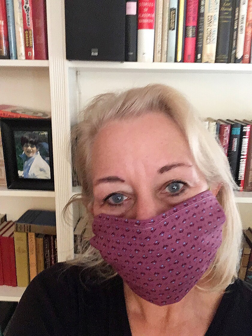 Laura Lipppman sports a no-sew mask she learned how to make on Twitter out of a quilt she started 37 years ago.