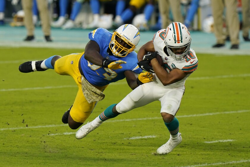 Chargers defensive tackle Justin Jones attempts to tackle Miami Dolphins running back Malcolm Perry.