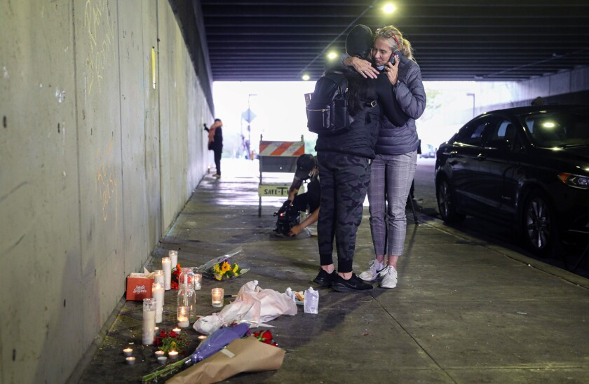 Amie Zamudio and Nina Hermosura embrace in front of a make-shift memorial under the City College bridge in San Diego.