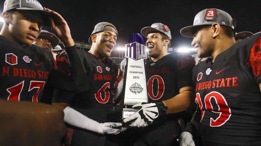 Aztecs players hold the trophy as they celebrate their 27-24 win over Air Force to win the Mountain West conference championship.