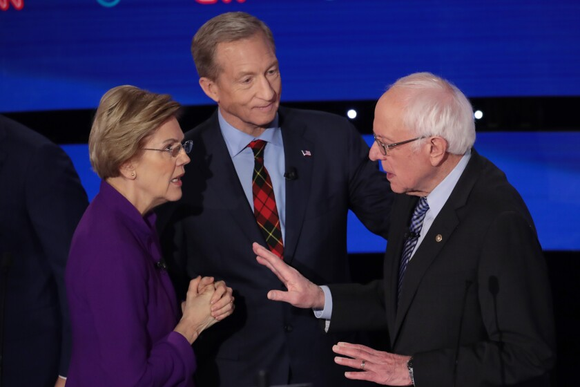 Elizabeth Warren and Bernie Sanders speak as Tom Steyer looks on after the Democratic presidential primary debate Tuesday night in Des Moines.