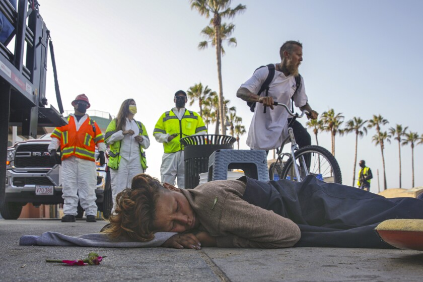 A homeless person sleeps on the boardwalk in Venice.