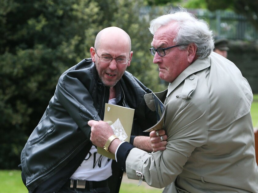 """Canadian Ambassador to Ireland Kevin Vickers, right, wrestles with a protester during a State ceremony to remember the British soldiers who died during the Easter Rising at Grangegorman Military Cemetery, Dublin Thursday May 26, 2016.  Vickers helped subdue a demonstrator who began chanting """"insult"""